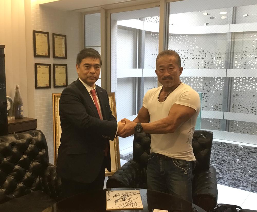 握手する角田信明師範とアクアバンク代表の竹原